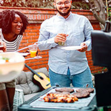 young people laughing and talking around a grill