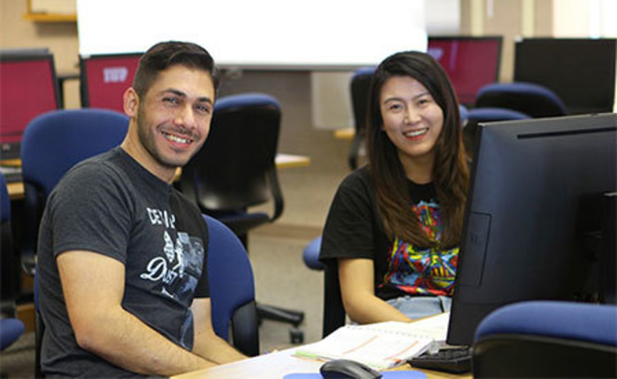 a Writing Center tutor and the student being helped pose in the Writing Center