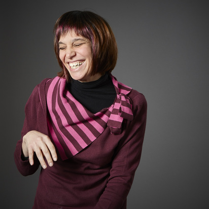 Maria, an Upstream Arts adult participant with a sholder length brown and purple shoulder-length bob and matching top laughs with her eyes closed, looking off to the side.