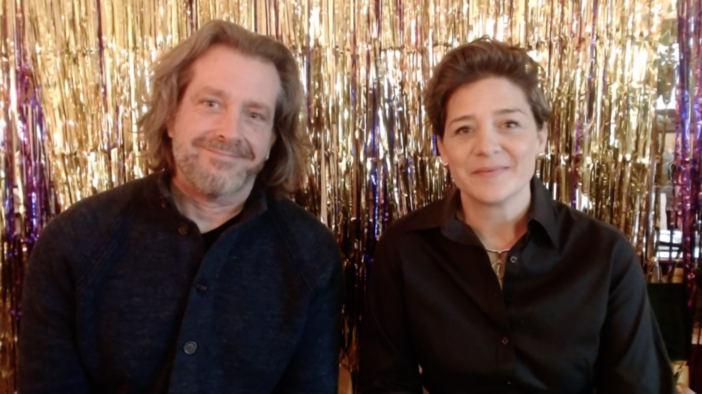 Screenshot of Matt and Julie Guidry in front of a gold and purple curtain, from event.