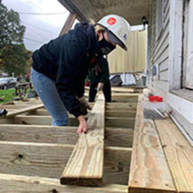 student moves wood into place on a deck she is helping to build