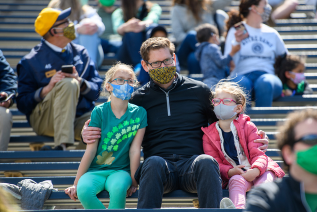 Family of three poses for a camera while watching Blue-Gold Game.