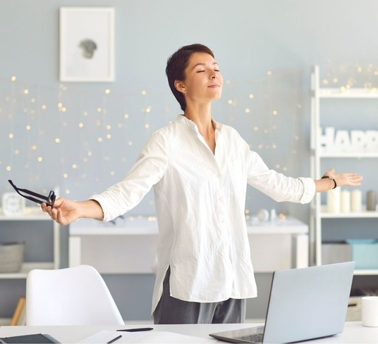 Woman taking a mini break at work by standing at her desk and breathing in deep.