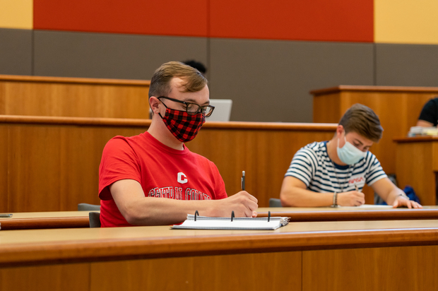 Photo of two masked male Central College students taking notes in class