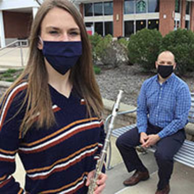 Maggie Weader, standing and holding a flute in the foreground, with her Guide, Adam Jones, seated, outside Cogswell Hall