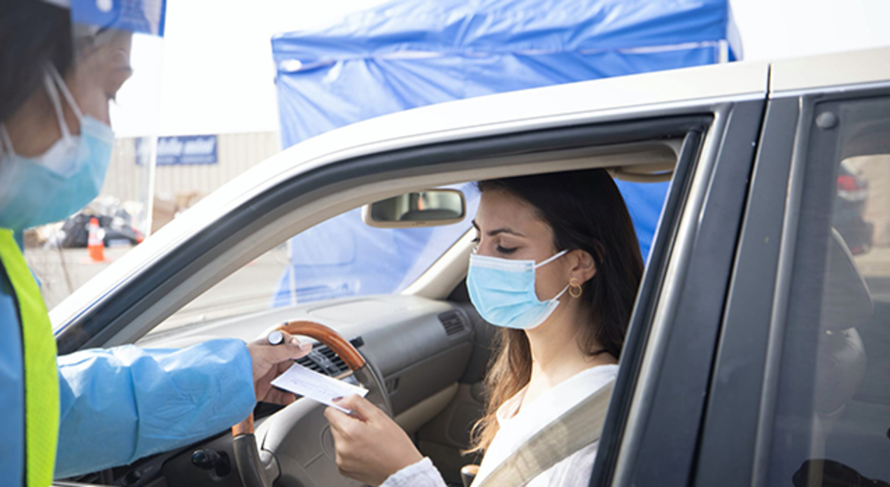A woman sitting in her car presents her COVID vaccine card to a staff member at a vaccine clinic