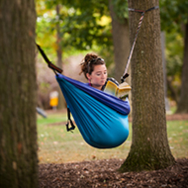 A student reads a book in her hammock, hung between the trees.