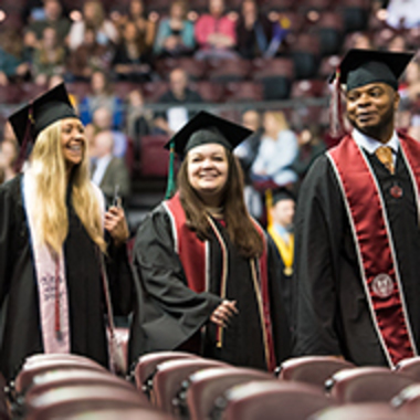 Three graduates in caps and gowns walk in a line to get their diplomas.