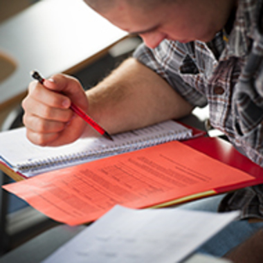 A student at a desk writes in a notebook and looks at exam questions.