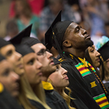 A row of graduate students looks up at the speaker during commencement ceremonies.