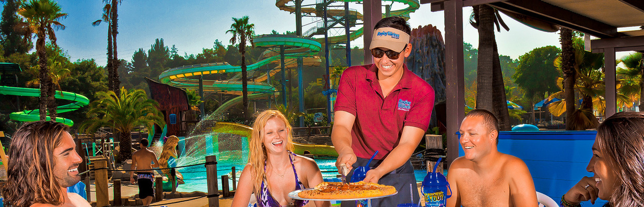 Raging Waters staff serving pizza to a grou of people