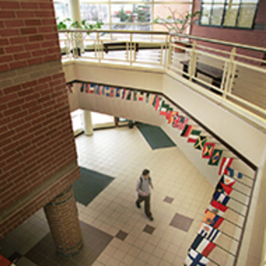 A lobby space inside the Eberly College of Business and Information Technology features a balcony trimmed with mini flags representing countries from around the world.