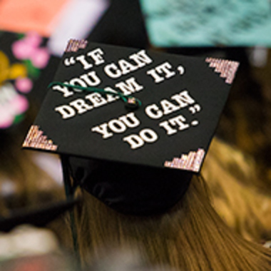 A graduate cap on a student's head at commencement as seen from above with the words
