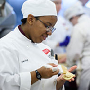 Woman in chef's jacket filling a pastry