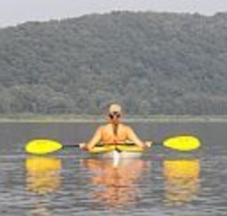 A kayaker resting on a wide body of water admiring the mountainside in the distance in front of them