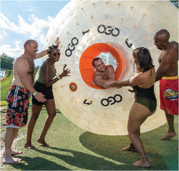 Two couples in bathing suits laughing and pulling another friend from a giant plastic OGO ball near the water
