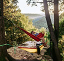 Person relaxing in a tree-to-tree hammock overlooking a scenic mountain valley