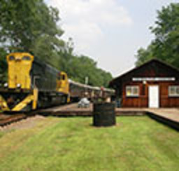 A yellow and black train idles outside an old restored train station