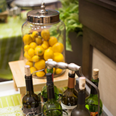 A photo of some wine bottles and a large glass jar full of lemons