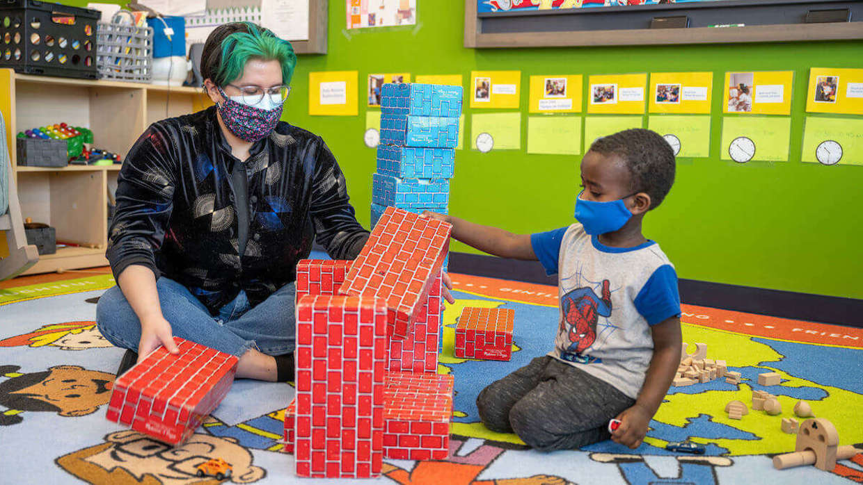 Adult plays with child at the Robinson Community Learning Center.