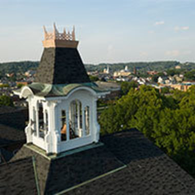 drone image of the Sutton Hall bell tower on a sunny day with the town landscape visible behind it