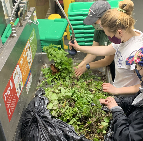Volunteers put weeds into a machine that turns the greens into energy for campus.