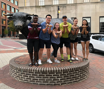 6 students posing in front of bull statue in Downtown Durham