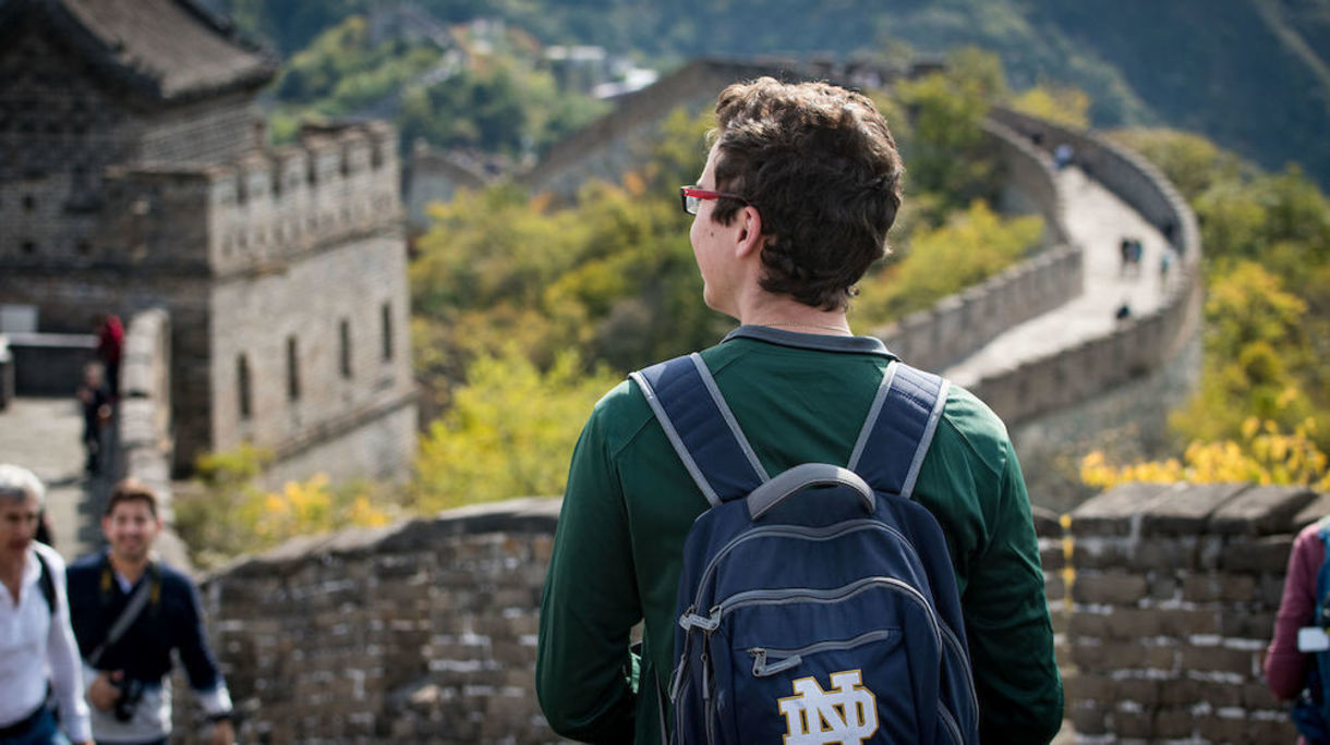 Student with ND backpack stands on the Great Wall of China.