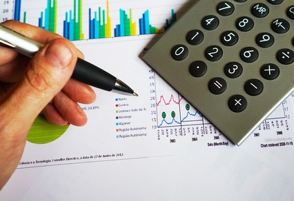 Image of person holding a pen and using a calculator to determine interest rates
