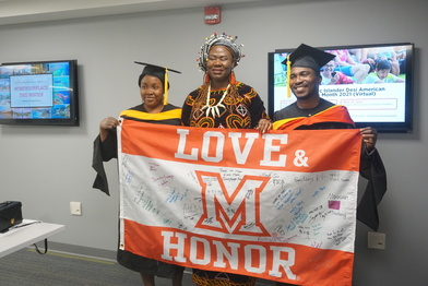 Grads holding up the Love and Honor flag