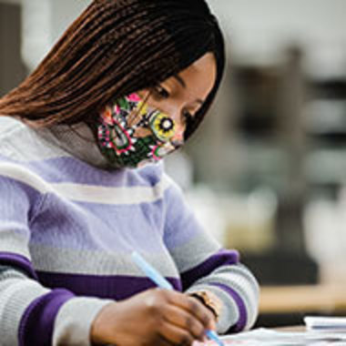 student with face covering studying