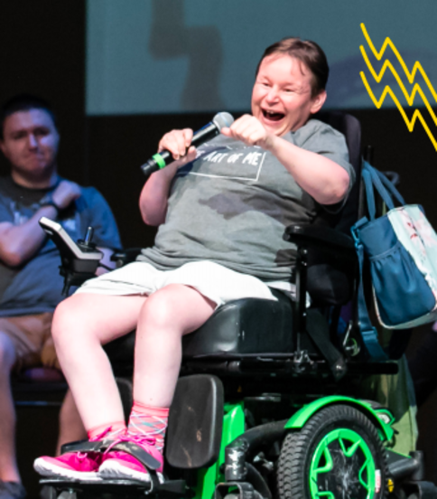 An adult participant using a powerchair holds the mic onstage during one of our Art of Me performances. They are speaking and making a powerful arm gesture.