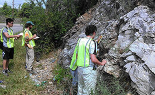 three geoscience students examine a large rock mass along the side of a road