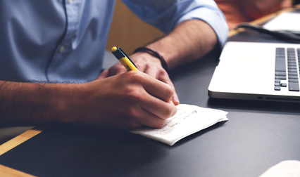 Photo of a person writing down important dates and information