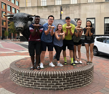 six students in front of bull statue in downtown Durham