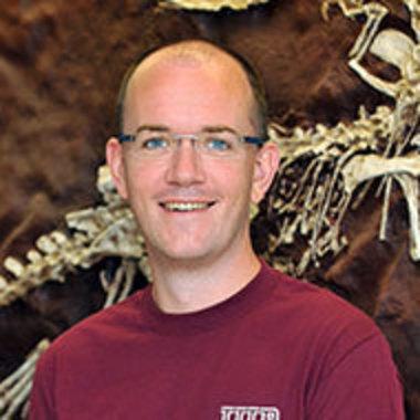Jonathan Warnock portrait in front of a dinosaur skeleton
