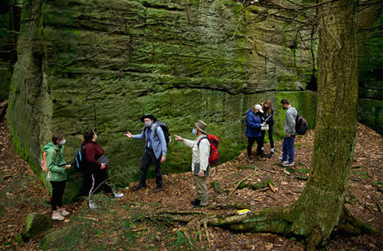 Faculty members Ken Coles and Jon Lewis discuss with two of five students in the scene what looks like a wall of rock at Bilger's Rocks in Clearfield County