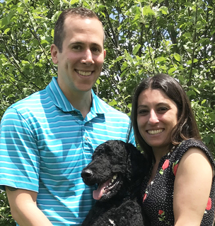 Photo of Dan Quimby and his wife Nicole with a large, curly haired black dog.