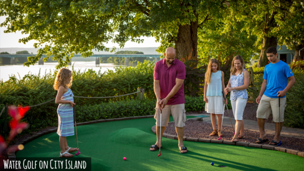 Family members watch as dad attempts a putt on a mini golf course with the Susqhehanna River visible in the background