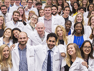 A large group of first-year Ph.D. students in lab coats posing after a lab coat ceremony.