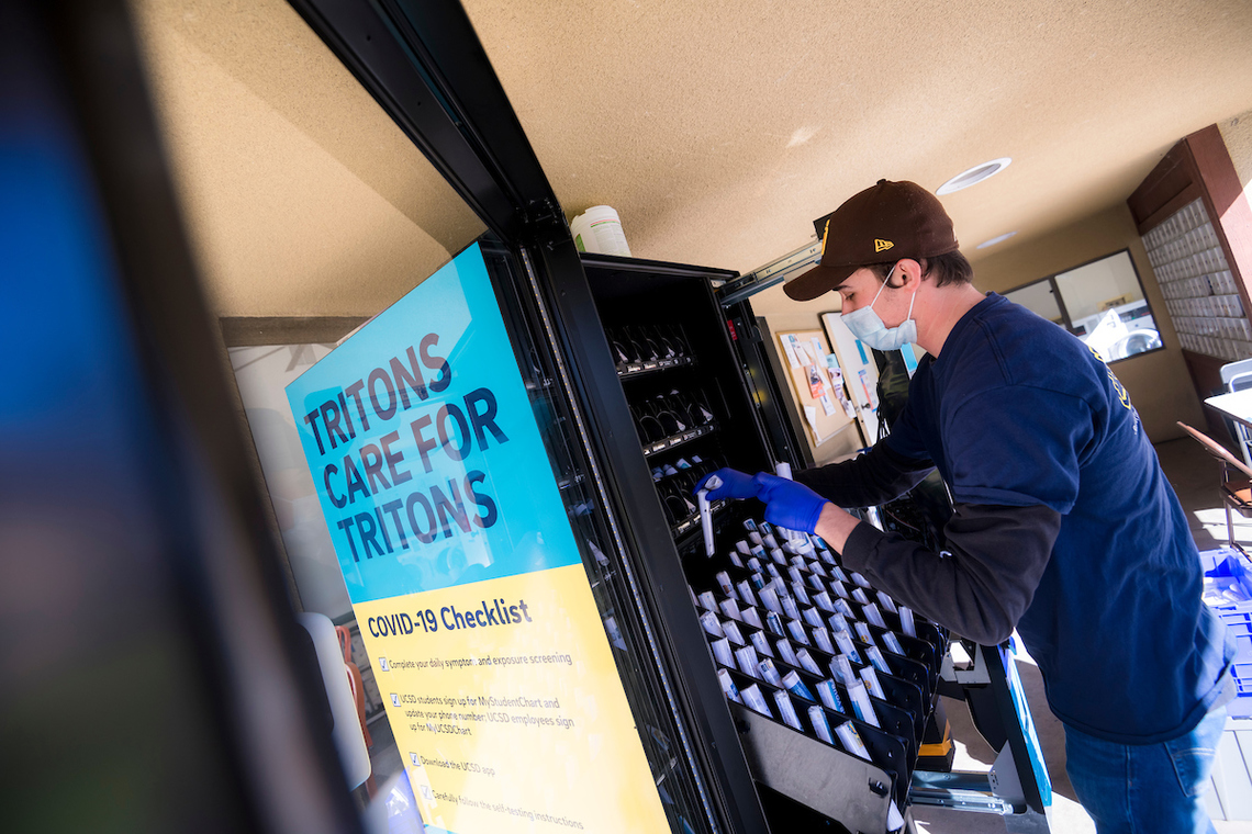 UC San Diego staff member stocking the self-administered COVID-19 test kits in a vending machine.