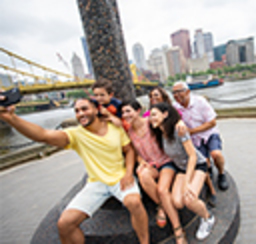 A group takes a family partrait selfie with the river, bridge and city behind them