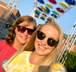 Two ladies smiling while taking an outdoor selfie with a colorful background of aerially suspended umbrellas in the downtown area behind them.