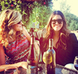 Two women smiling and sharing a bottle of wine and a local winery