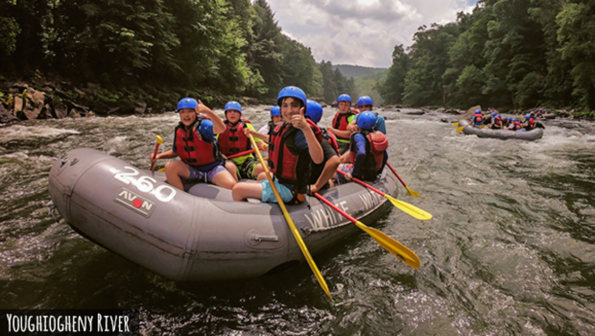 An inflatable watercraft on the Youghiogheny River with enthusiastic rafters giving thumbs-up as they hold their paddles