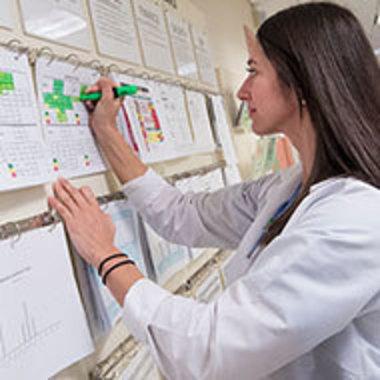student in nursing uniform using highlighter marker on wall charts