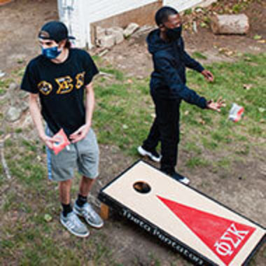 two students, one in a fraternity T-shirt, play cornhole in a yard