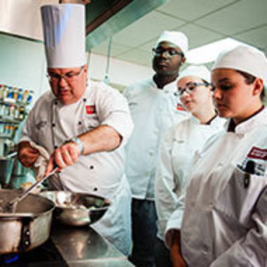 Chef Andrew Nutter provides hands-on instruction to three culinary students
