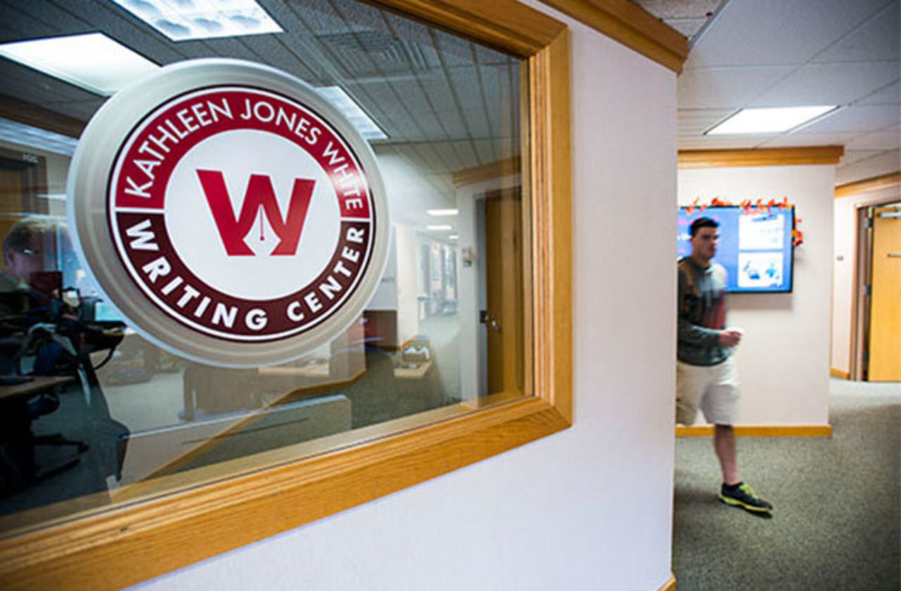 circular Jones White Writing Center sign appears in a writing center window as a student comes around the bend