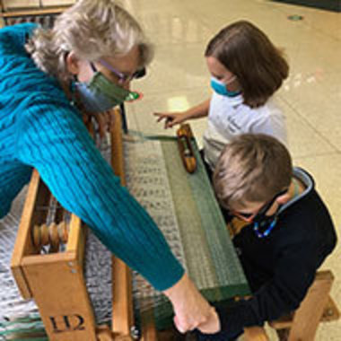 artist Sandy Trimble shows two children how to weave using a loom